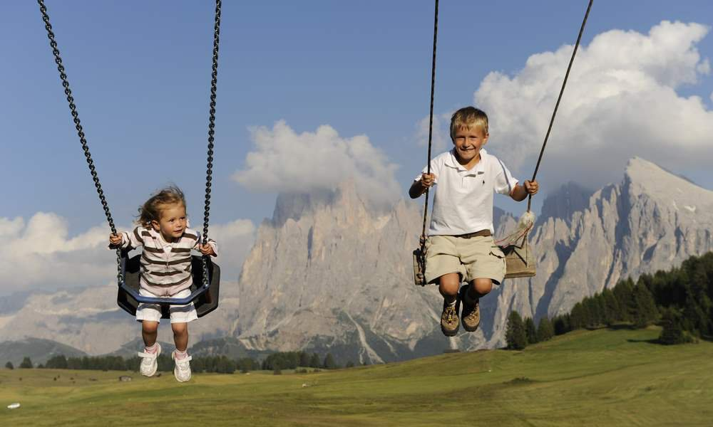 Gioco e divertimento per i piccoli ospiti nel parco giochi del maso durante una vacanza in famiglia a Castelrotto